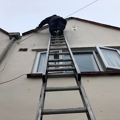 Gutter being cleaned while on ladder In Bracknell